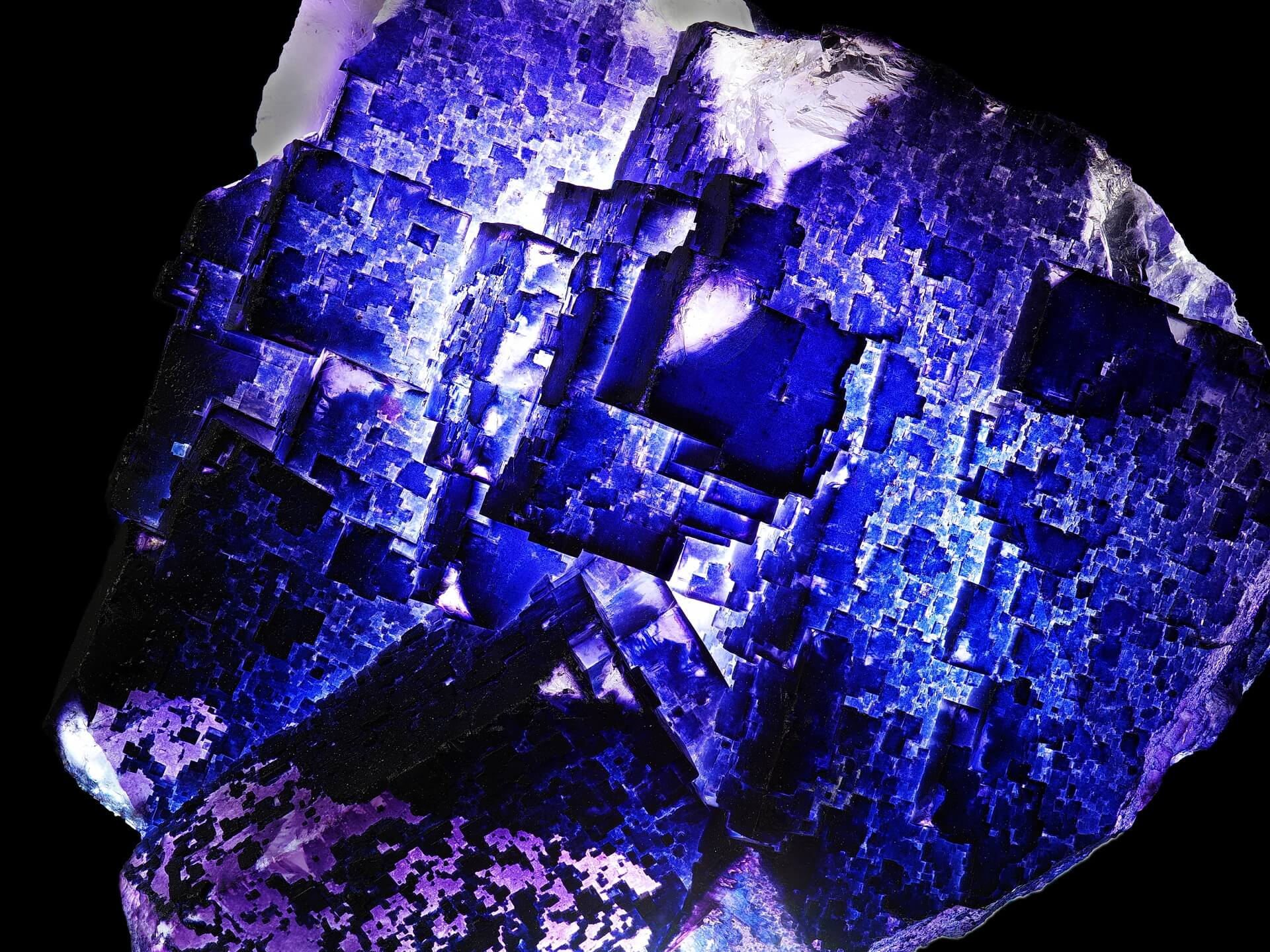 Light shines through a purple cubic specimen, looking almost like a futuristic city seen from above.