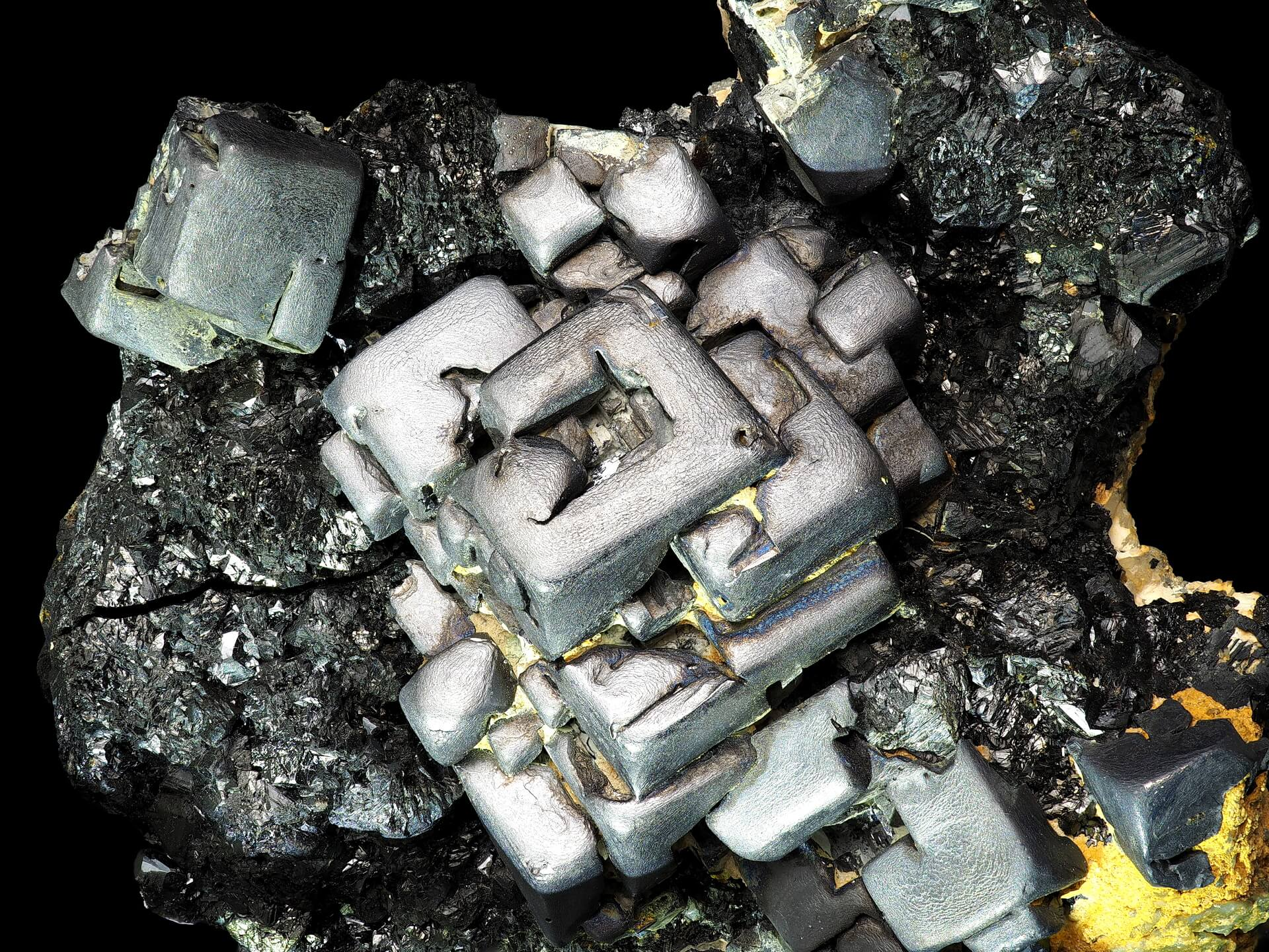 Large square Galena crystals are stacked upon each other, with the top crystal showing hollow skeletal form.