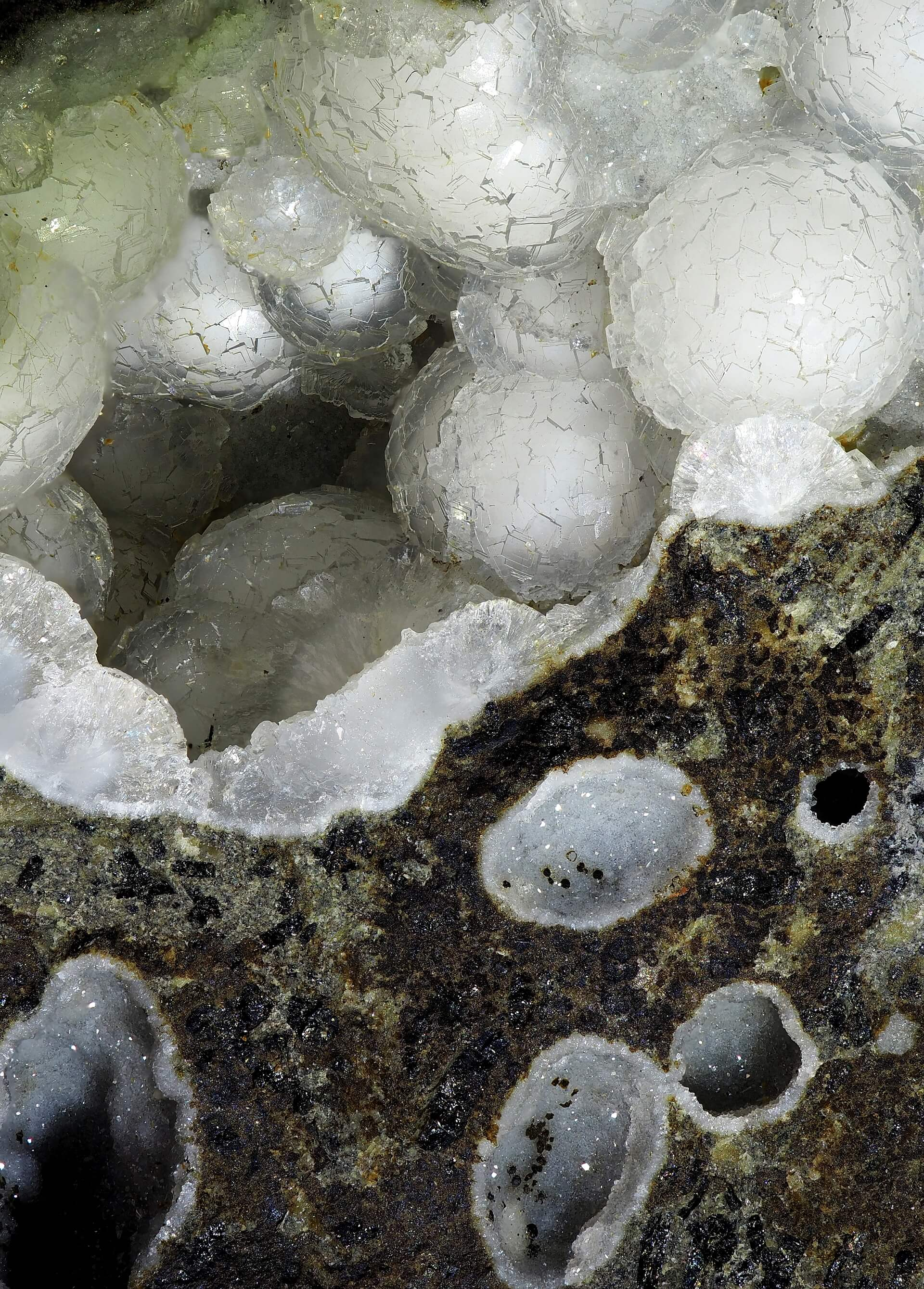 Many tiny Basalt vugs lined with Thomsonite crystals. One vug features large white balls of Thomsonite with a texture resembling a football (soccer ball).