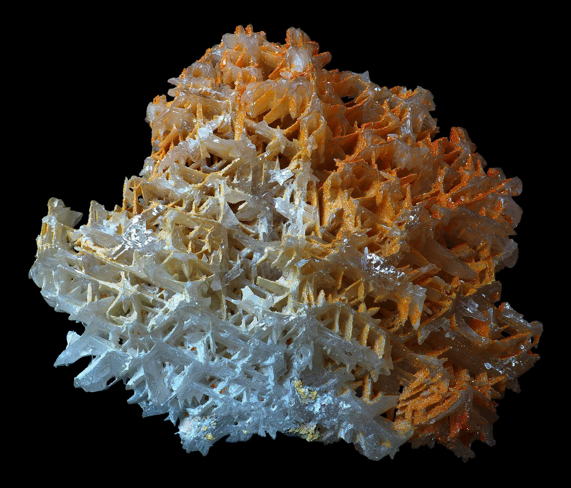 Interconnecting white Cerussite crystals with partial orange Wulfenite coating.