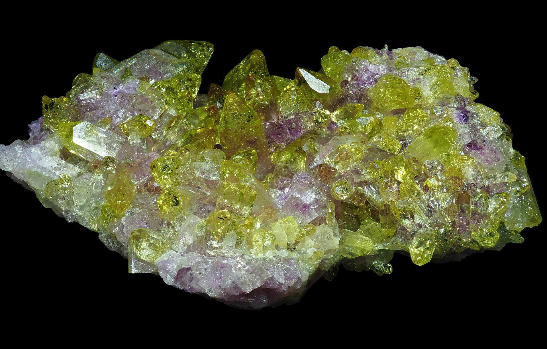 Clear yellow Vesuvianite crystals on a pink Manganoan base.